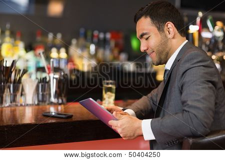 Attractive businessman sitting at bar reading drinks menu