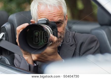 Paparazzi taking picture with his professional camera hiding himself in his car