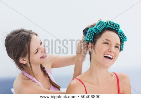 Girl fixing her friends hair rollers at home in bedroom at sleepover