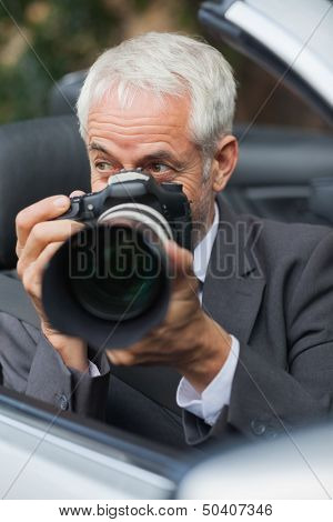 Mature paparazzi taking picture with his professional camera hiding himself in his car