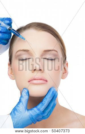 Relaxed attractive model on white background having botox injection on the forehead