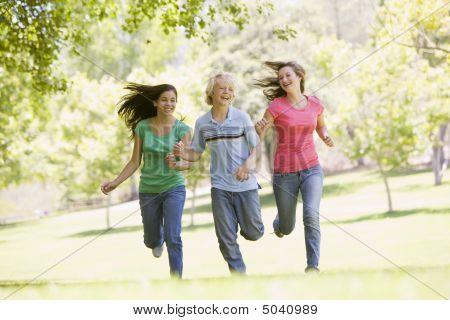 Teenagers Running Through Park