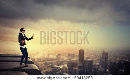 Image of businesswoman in blindfold standing atop of building
