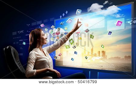 Young woman in armchair pushing icon on media screen