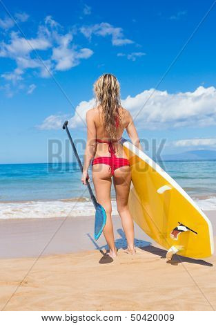 Attractive Woman with Stand Up Paddle Board, SUP, on the beach in Hawaii