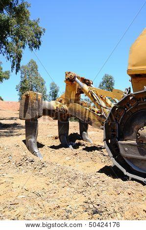 Ripper tool on yellow bulldozer.