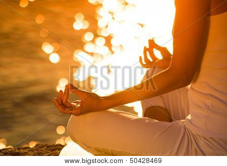 Attractive young woman in a yoga position on a beautiful beach