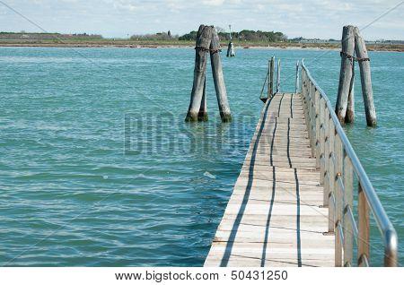 Small Bridge Over Blue Laguna Water In Venice
