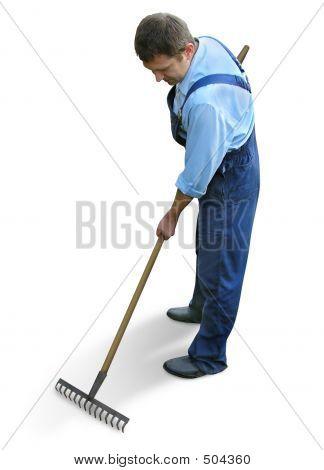 Gardener - Worker In Working Clothes, Raking The Garden