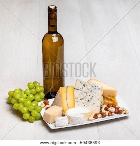 wine bottle and different kinds of cheese