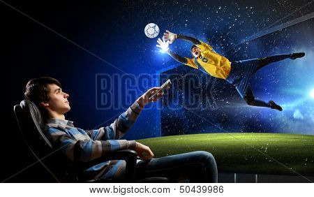 Young man watching football match on TV