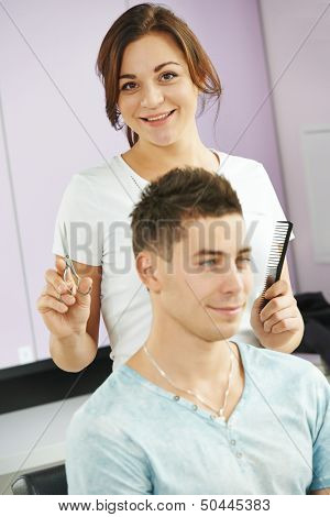 Female hairdresser with scissors and comb with man client in beauty parlour salon