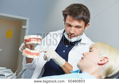 Dentist explaining dental treatment to patient with fake denture