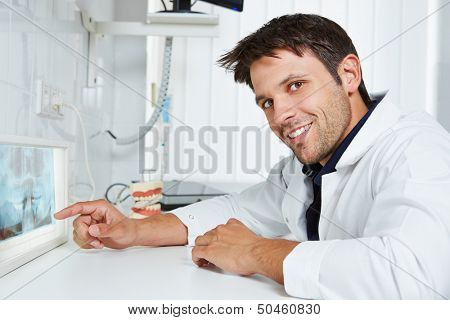 Dentist pointing with his finger at x-ray image in dental practice