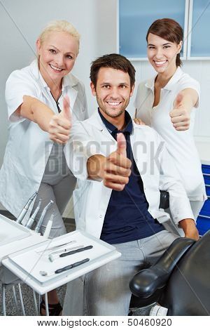 Happy team at dentist holding their thumbs up in dental practice