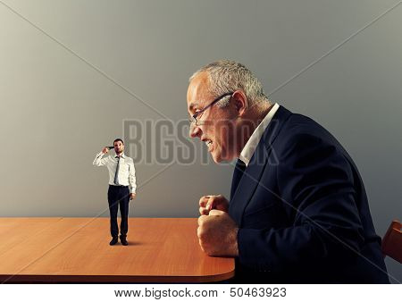 irritated boss looking at unhappy man with gun