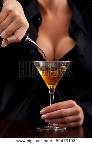 Barmaid stands behind bar mixing drink for client