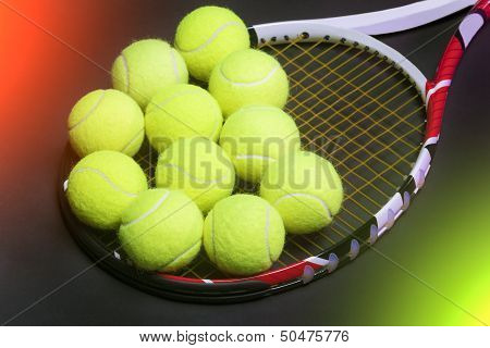 Plenty Of Tennis Balls On Tennis Racquet Strings Against Black Background. Light Effects Used