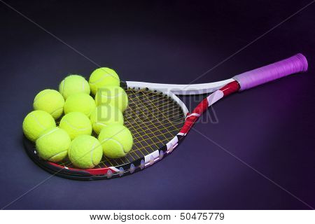 Plenty Of Tennis Balls On Tennis Racquet Strings Against Black Background