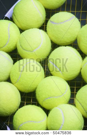 Plenty Of Tennis Balls On Raquet Strings