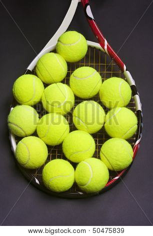 Tennis Racket With A Lot Of Tennis Balls On It
