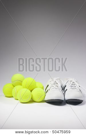 Tennis Concepts: Tennis Sneakers And Balls Together Against White. Vertical Image