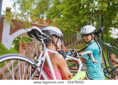 Two Caucasian Sportswomen Work Out With Bicycles