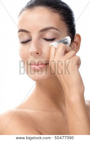 Attractive young female removing eye makeup by cotton wool.