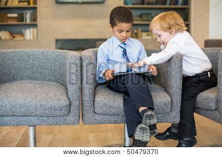 Caucasian boys and mulatto in the business clothing uses tablet in the business center