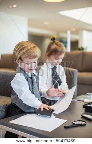 Boy and girl in business suit playing with stationery in a business center, boy uses a puncher.