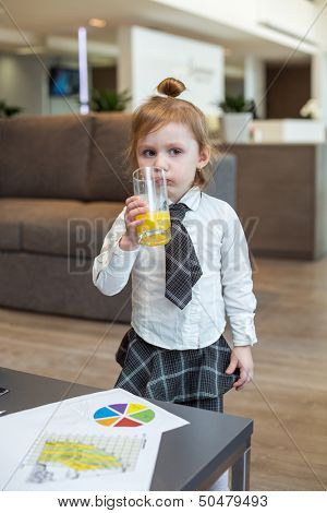 A cute little girl in a business clothes drinking juice in the business center