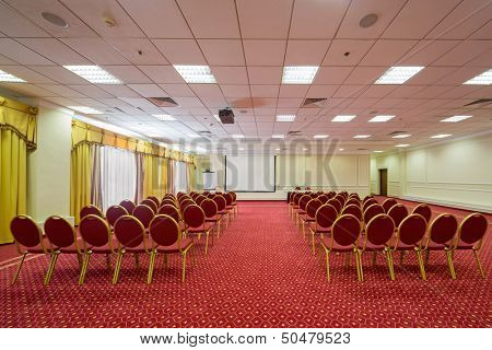 Screen, chairs and projector in empty conference hall with a red carpet on the floor