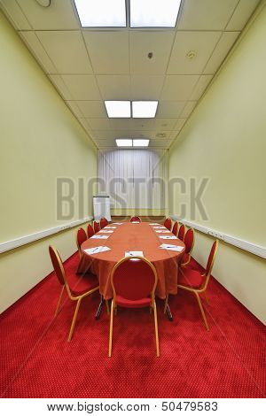 Chairs and table in modern empty conference room with a red carpet on the floor