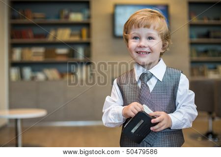 Little boy in business clothes with a puncher in the business center