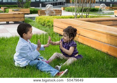 Brother and sister sitting on the grass and clap each other hands