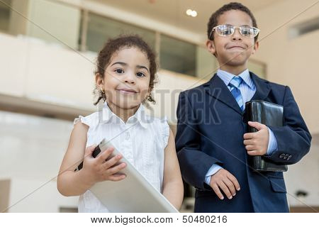 Little boy and girl in business clothes in the business center with communication devices, focus on a girl.