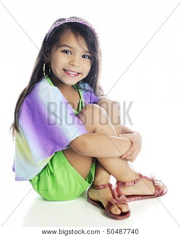 A beautiful young elementary girl with long, brown hair sitting with her arms wrapped around her legs.  On a white background.