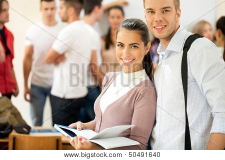university students couple  with book in classroom