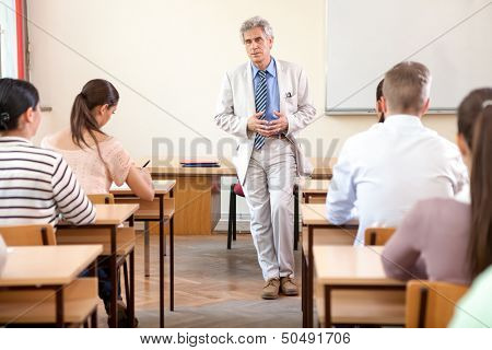 Group of students study in classroom at high school with professor