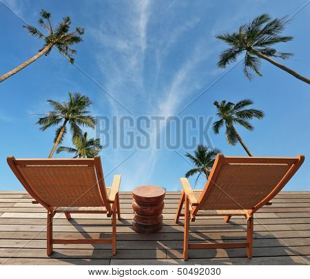 Two convenient comfortable guest sun loungers and a bedside table are worth on a wooden platform. The excellent overview of the blue sky, white clouds and swaying palm trees