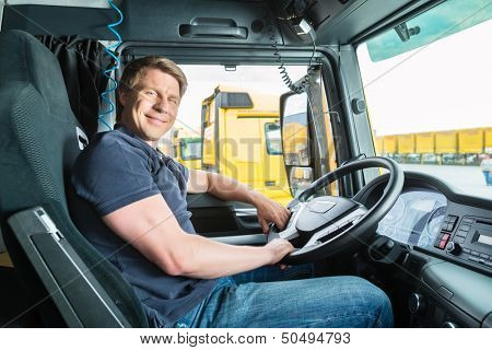 Logistics - proud driver or forwarder in drivers cap of truck and trailer, on a transshipment point