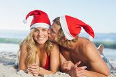Man giving kiss to partner wearing christmas has on beach
