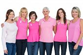 Happy women wearing pink for breast cancer awareness on white background