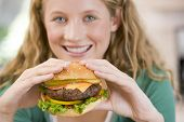 stock photo of teenage girl  - Teenage Girl Eating Burgers - JPG