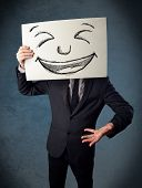 picture of faceless  - Businessman holding a paper with a drawed smiley face on it in front of his head - JPG