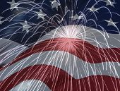 stock photo of superimpose  - Picture of an american flag superimposed over a picture of exploding fireworks - JPG