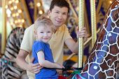 stock photo of merry-go-round  - happy smiling son and his handsome father spending fun time together at amusement park riding merry - JPG