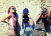 stock photo of funky  - urban girls have fun with vintage photo cameras outdoor near grunge wall - JPG