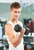 stock photo of triceps brachii  - bodybuilder man at biceps brachii muscles exercises with training dumbbells in fitness gym - JPG