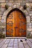 stock photo of arch  - Beautiful old wooden door with iron ornaments in a medieval castle - JPG